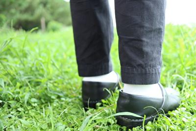黒いダンスコの靴を履いている自分の足元を踵側から見た写真