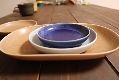 イイホシユミコのオーバル型の薄茶色のお皿の上に丸い薄水色と濃い青の豆皿を重ねている写真