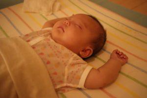 娘が両手を上に上げて寝ている写真