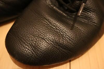 黒いジャズシューズの表面の皺