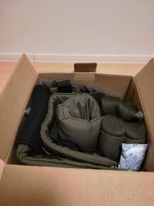 箱の中に入っているカーキ色の抱っこ紐