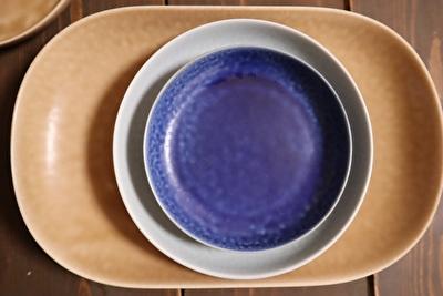 イイホシユミコのオーバル型の薄茶色のお皿の上に丸い薄水色と濃い青の豆皿を重ねて上から撮った写真