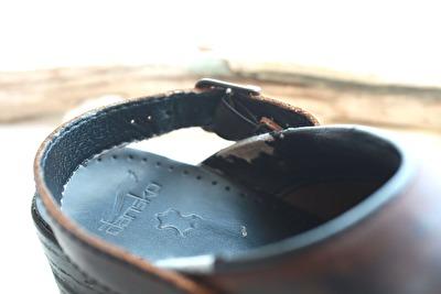 ダンスコの茶色い靴の足かけベルトをかかと部分に出している写真