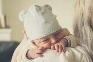 お母さんに抱っこされている白いクマの帽子をかぶった赤ちゃん