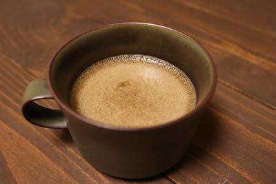 オクシモロンの緑のティーカップに飲み物を入れている写真