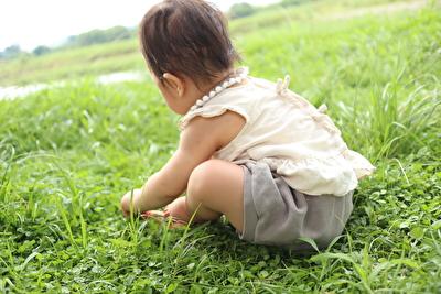 monmimiのグレーのブルマとキナリのブラウスを着て外で葉っぱを摘んで遊んでいる娘の写真