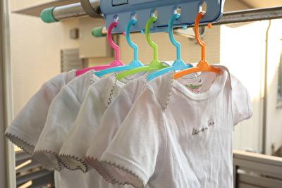 ダイソーで買った赤ちゃん用ハンガーフックに5枚の白い肌着をかけている写真