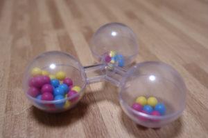 100均で買った透明で透明の3つの丸の中に小さいピンクと水色と黄色のビーズがたくさん入っているおもちゃ