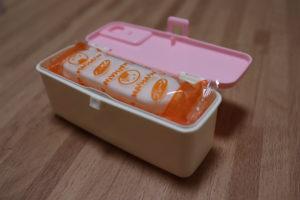 100均で買った赤ちゃん用ピンクの長方形のおせんべいケースに実際におせんべいを入れている写真