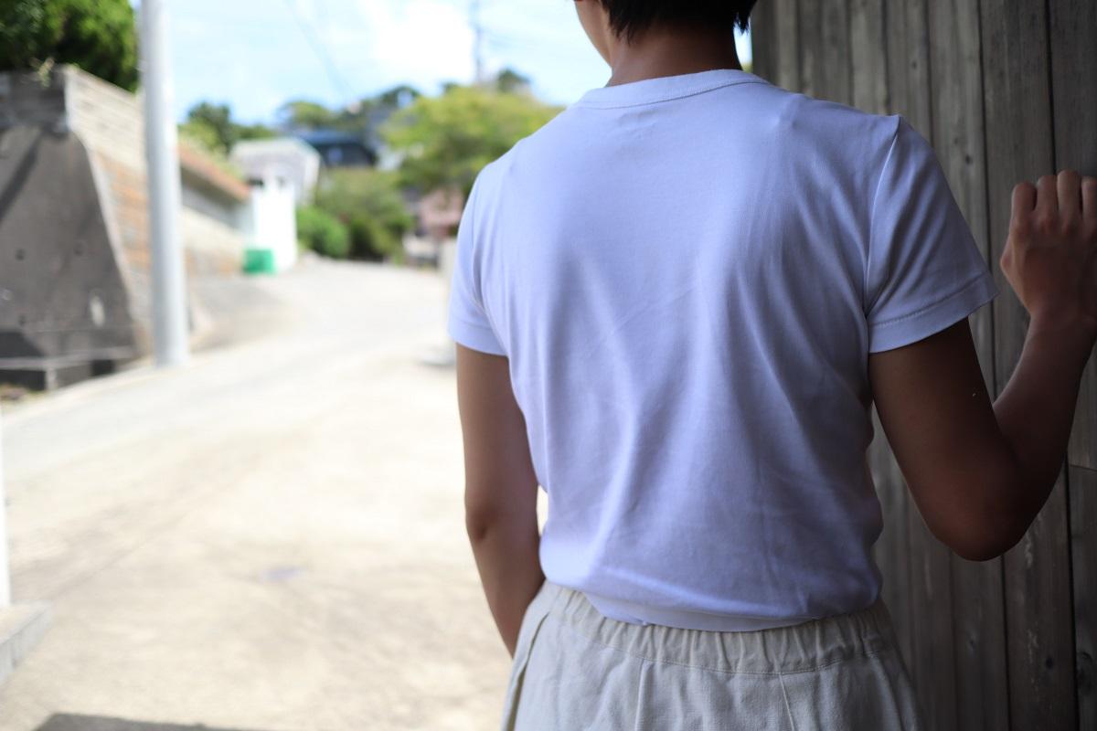 白いTシャツとキナリノパンツを着てい後ろを向いている自分の写真