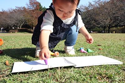 100均のらくがき帳に外で絵を描いている娘の写真
