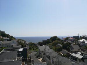 家のベランダから見た他の家と少し遠くに見える海の写真