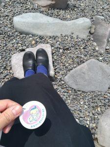 砂浜で石の上に座りマタニティマークを持っている写真