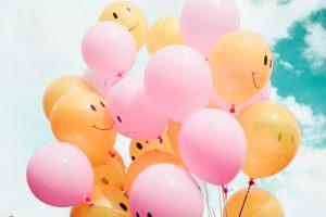 空に浮かぶピンクと黄色のにこちゃんマークのついた沢山の風船