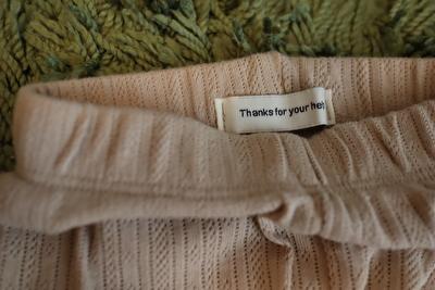 カギ編みのベージュの赤ちゃん用レギンスのタグの写真