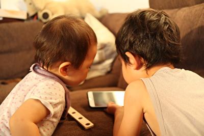 娘と甥っ子がケータイを見ている後ろ姿の写真