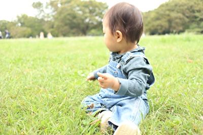 広い草原に娘が座っている写真