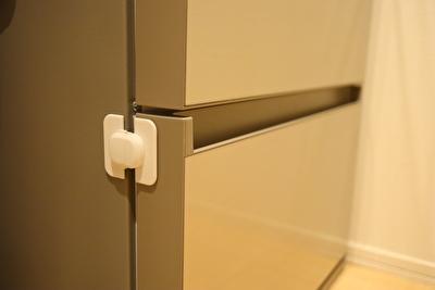 セリアで買った冷蔵庫引き出サイドロックを冷蔵庫に貼っている写真