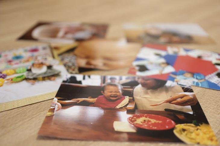 娘の写真6枚を床に乱雑に並べている写真