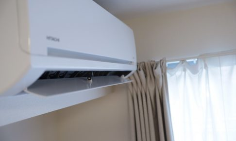 白いエアコンとベージュのカーテンの写真