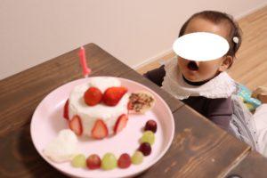 お誕生日ケーキを前にしてお口を開けている娘の写真