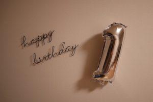 HappyBirthdayの文字のワイヤーアートと1の数字のシルバーのバルーンを白い壁に飾っている画像