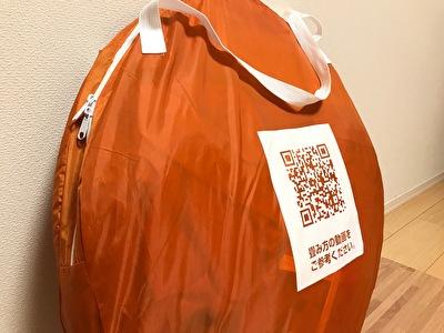 オレンジのポップアップテントをケースに入れた状態の写真