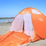 オレンジのポップアップテントを海で広げている写真