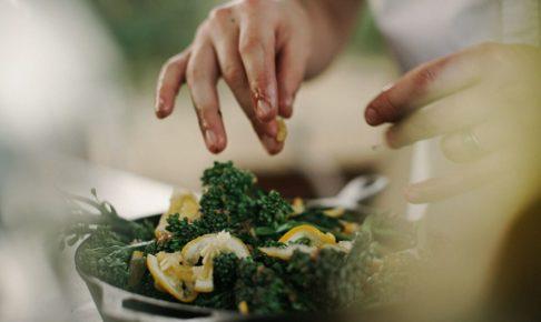 お鍋の中に野菜を入れている人の手の写真