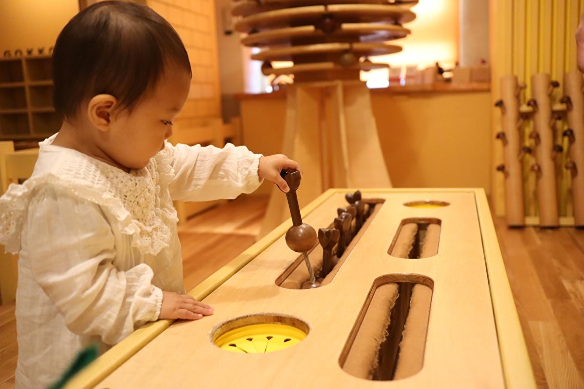 木のおもちゃで遊んでいる娘の写真