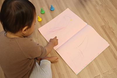 100均のらくがき帳とベビーコロールのクレヨンでお絵描きしている娘の写真