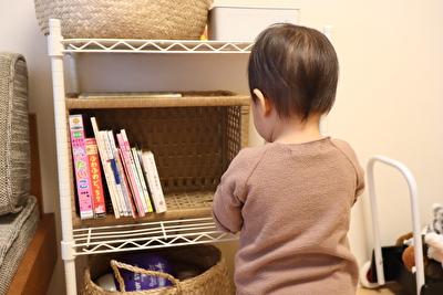 白いラックの前でおもちゃを選ぶ娘の写真