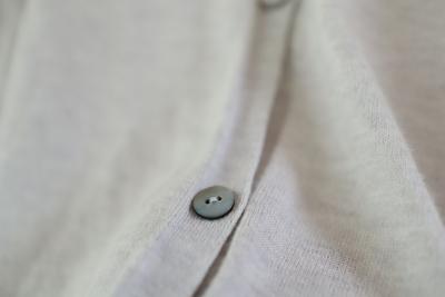 evamevaの綿の薄いグレーのカーディガンのボタンのアップ