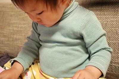 プチバトーベビーの緑のボーダーの長袖ボディ肌着を着ている娘の上半身の写真