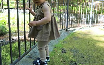 ZARABABYの茶色いタンクトップをベージュのレギンスを履いている娘の横からの全身の写真