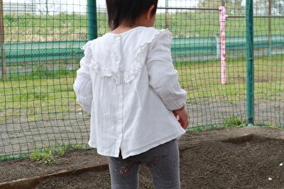 ZARABABYの白いいブラウスを着ている娘の後ろ姿の写真