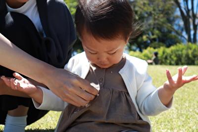 ZARABABYの茶色いタンクトップと白いカーディガンを着ている娘