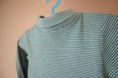 プチバトーベビーの緑のボーダーの長袖ボディ肌着の襟を折っている写真