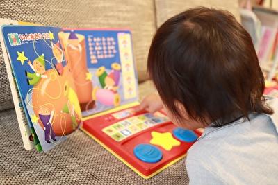 おづよう絵本で遊んでいる娘の後ろ姿の写真