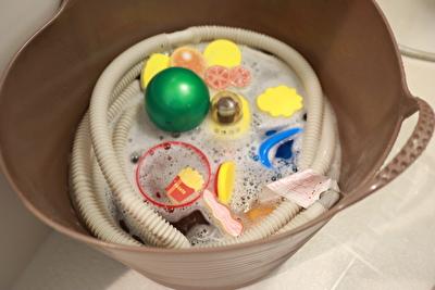 茶色いバケツにオキシクリーンを入れて洗濯機のホースと子供用のおもちゃを漬けている写真