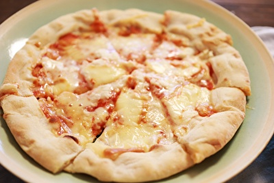 薄い水色の丸いお皿にのせたピザ