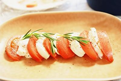 イイホシユミコの茶色い楕円形のお皿にのせたトマトのカプレーゼ