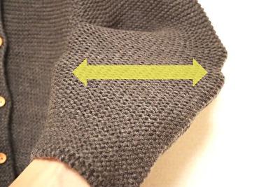 ZARABABYの3-4歳用のグレーのニットカーディガンの袖部分に手を入れて伸ばしている写真