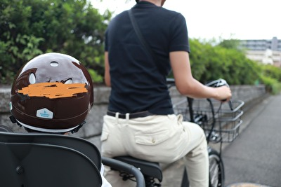 グレーの電動自転車に乗っている私とnicco×こどもビームスの茶色いヘルメットをかぶっている娘の後ろ姿