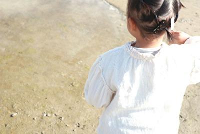 の白いブラウスを着ている娘の後ろ姿の写真