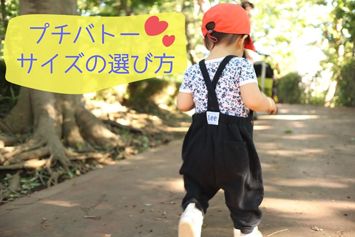 ZARABABYの麦わら帽子と紺色のサロペットを着ている娘の後ろ姿