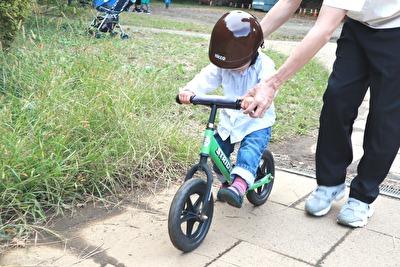緑色のストライダーに乗ってNICCO×ビームスの茶色いヘルメットをかぶっている娘の写真