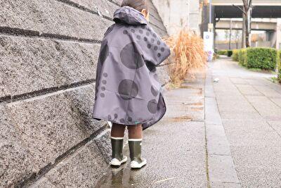 392の黒の水玉のレインポンチョを着ている娘の後ろ姿