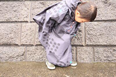 392の黒の水玉のレインポンチョを着ている娘の正面の姿