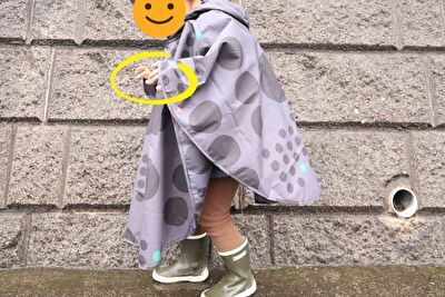 392の黒の水玉のレインポンチョを着ている娘の横姿